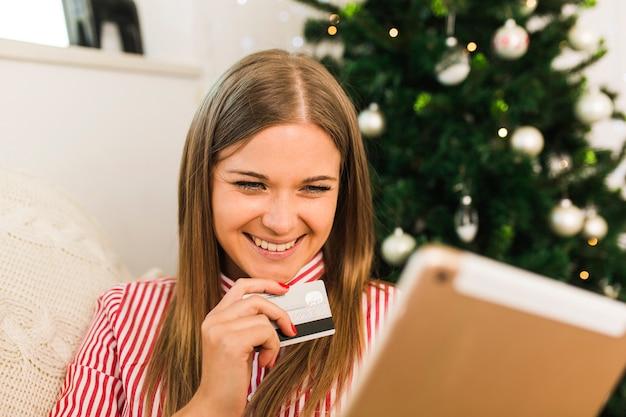 De vrolijke tablet van de dameholding en creditcard dichtbij kerstboom