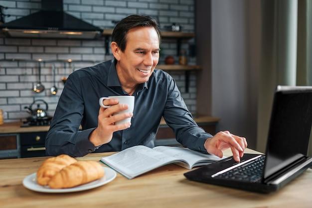 De vrolijke volwassen zakenman zit bij lijst in keuken. hij werkt met laptop en glimlacht. man houdt witte kop en typ op toetsenbord.