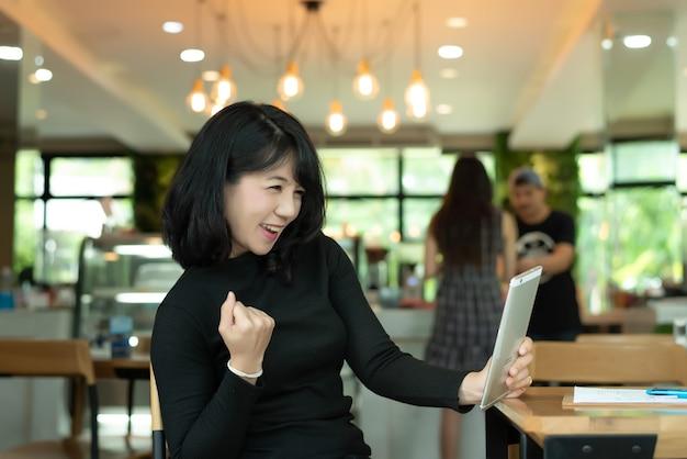 De vrolijke vrouw heft handen met geluk voor succesvol online project op