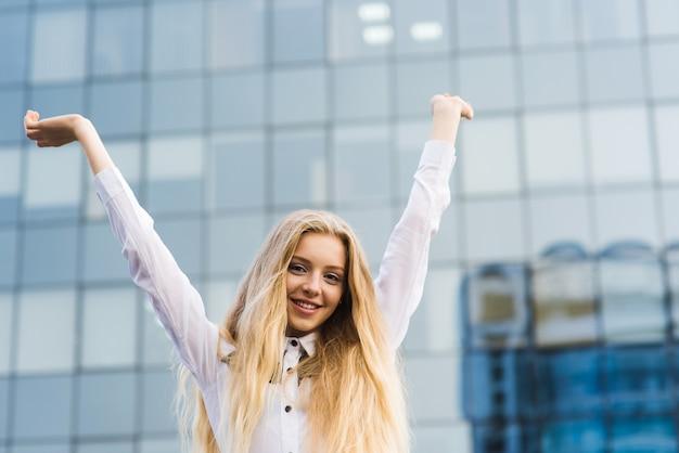 De vrolijke vrouw heft omhoog de stad in handen op