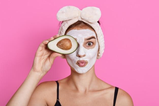 De vrolijke vrouw met kosmetisch masker op gezicht, dat kuuroordbehandeling doet, die oog behandelt met de helft van avocado, lippen rond houdend geïsoleerd op roze muur houdt, heeft perfecte verse huid.