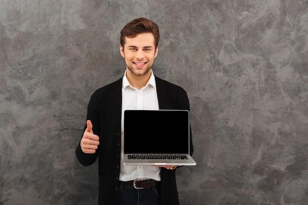 De vrolijke zakenman die vertoning van laptop tonen maakt duimen omhoog.