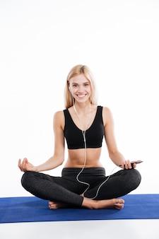 De vrolijke zitting van de geschiktheidsvrouw maakt yogaoefeningen