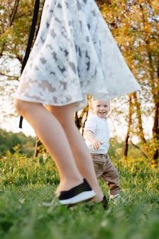De vrolijke zoon rent weg van zijn moeder terwijl hij haar inhaalt op het groene grasveld in het park