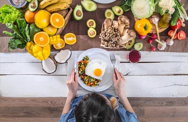 De vrouw aan de eettafel met biologisch voedsel, het uitzicht van bovenaf.