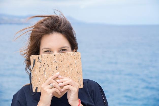 De vrouw bedekt haar gezicht verlegen met haar notitieboekje, waar ze al haar vertrouwelijkheid heeft opgeschreven.