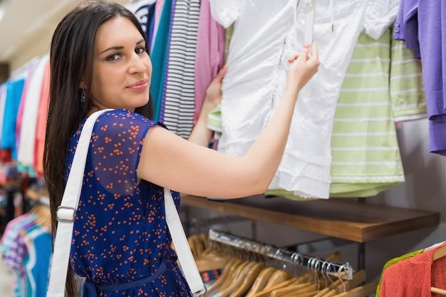 De vrouw bekijkt het prijskaartje en glimlacht