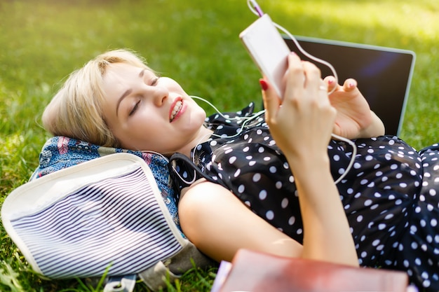 De vrouw bepaalt of ontspannend op groen gras luisterend aan muziek