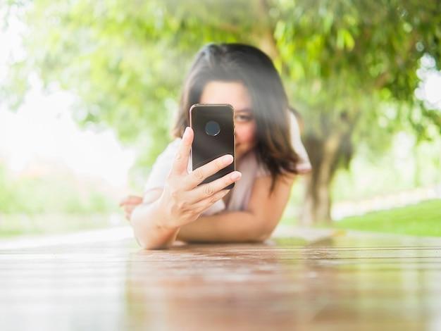 De vrouw bepaalt op houten terras nemend foto gebruikend mobiele telefoon in het groene park
