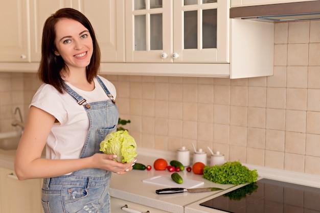 De vrouw bereidt groentesalade in de keuken voor. gezonde levensstijl concept.
