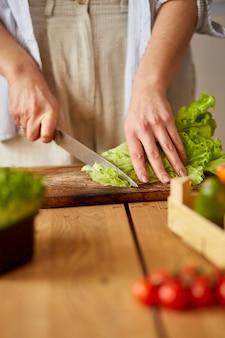 De vrouw bereidt groentesalade in de keuken voor