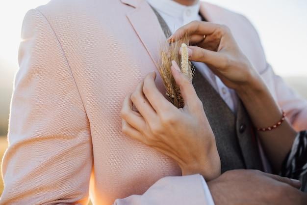 De vrouw bevestigt een modieus bruids knoopsgat aan een man