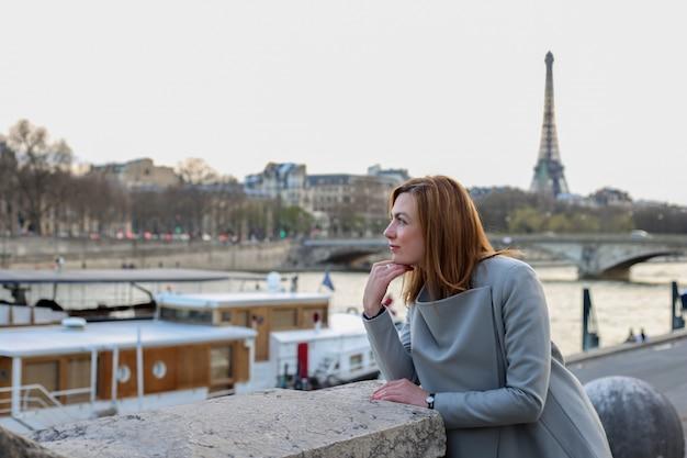De vrouw bevindt zich alleen dichtbij de rivier en de toren van eiffel in parijs