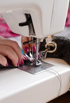 De vrouw bij de naaimachine herstelt de lederen tas. hand close-up