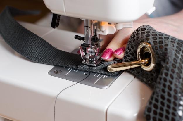 De vrouw bij de naaimachine herstelt de lederen tas