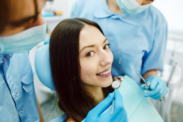 De vrouw bij de receptie bij de tandarts met assistente