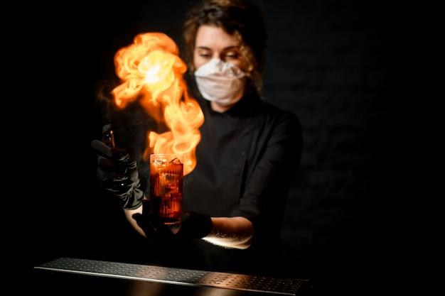 De vrouw bij donkere bar bestrooit op glas met alcoholische drank en maakt vuurvlam