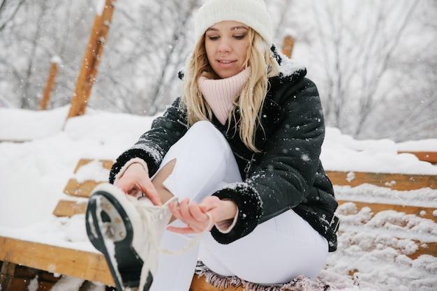 De vrouw bindt schoenveters bij kunstschaatsen bij ijsbaan. detailopname