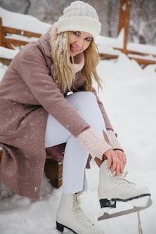 De vrouw bindt schoenveters bij kunstschaatsen bij ijsbaan.