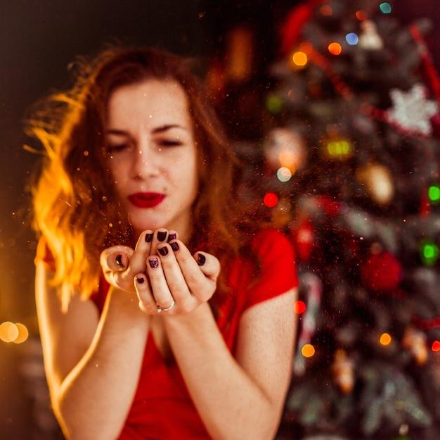 De vrouw blaast sneeuw van haar palmen die zich vóór de kerstboom bevinden