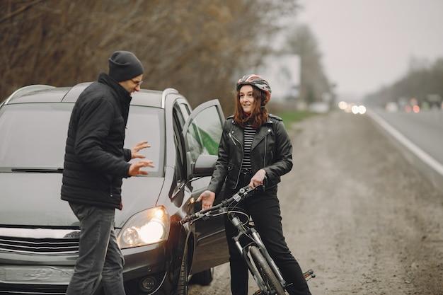 De vrouw botste tegen de auto. meisje in een helm. mensen maken ruzie over het ongeluk.