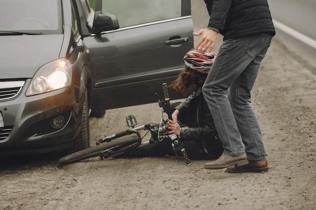 De vrouw botste tegen de auto. meisje in een helm.
