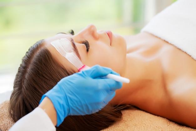 De vrouw brengt een spa-masker aan om de huid in de schoonheidsstudio te hydrateren en te verzorgen