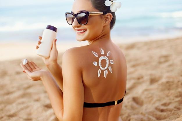 De vrouw brengt zonnecrème op gebruinde rug aan