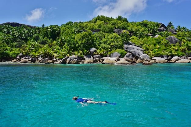 De vrouw die blauw materiaal draagt snorkelt in de turkooise blauwe wateren van een paradijseiland.