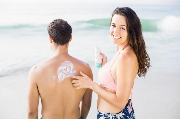 De vrouw die een hartsymbool maken bemant terug terwijl het toepassen van een zonneschermlotion