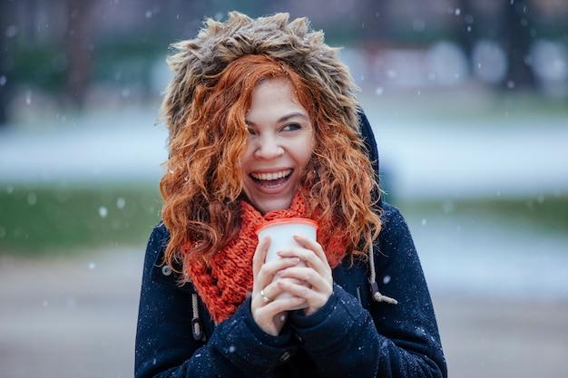 De vrouw die een kop houden van haalt thee op een sneeuwdag weg