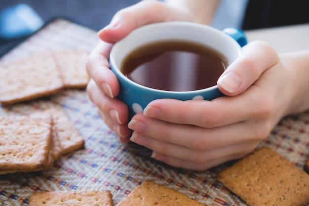 De vrouw die een kop van hete thee of koffie houdt, ligt naast koekjes, close-up
