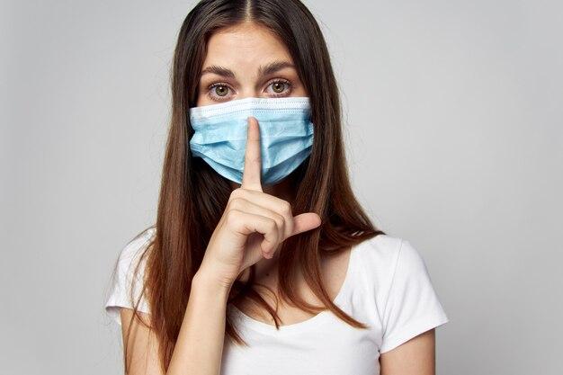 De vrouw die een medisch masker op haar gezicht draagt, houdt een vinger dichtbij haar hoofd kijk vooruit