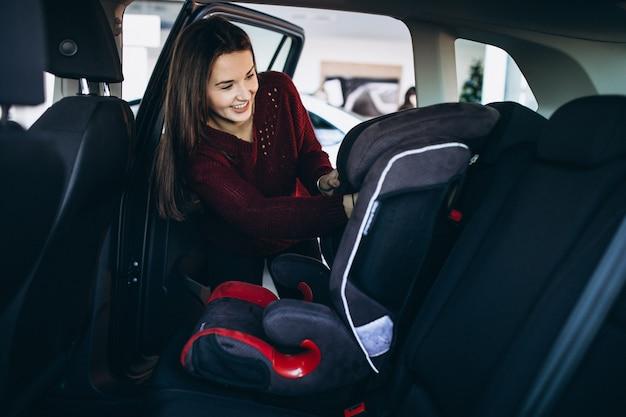 De vrouw die een veiligheidsauto installeert zit in een auto