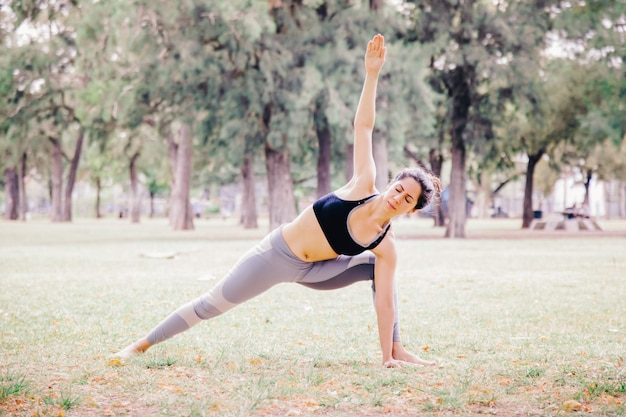 De vrouw die een zijplankyoga doet stelt in openlucht. pilates gezonde levensstijl voor mensen in yoga-oefeningen. buiten trainen en fit blijven concept. mensen die welzijnsmeditatie in het park doen.
