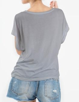De vrouw die grijze t-shirt draagt en scheurt jeans op wit kort