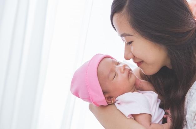 De vrouw die haar babymeisje houdt, sluit omhoog