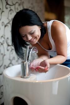 De vrouw die haar wast dient de gootsteen in