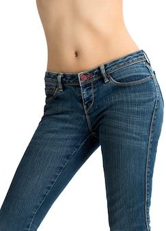 De vrouw die jeans draagt en toont gestemde die maag op witte achtergrond wordt geïsoleerd