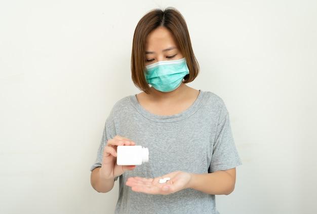 De vrouw die masker dragen voor beschermt coronavirus met het nemen van pil op wit.
