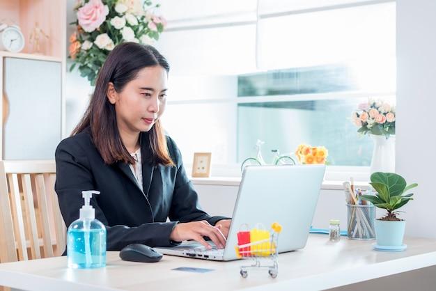 De vrouw die momenteel thuis werkt en online winkelt om zichzelf in quarantaine te plaatsen tijdens de uitbraak van de coronavirusziekte (covid-19)