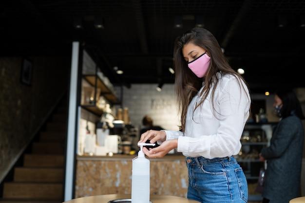 De vrouw die ontsmettingsmiddelgel gebruikt maakt handen schoon bij koffie.