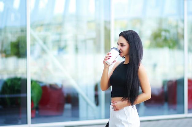 De vrouw die op de straat lopen met haalt koffie weg