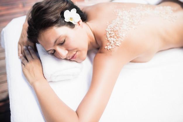 De vrouw die op massagelijst ligt met zout schrobt terug in een kuuroord