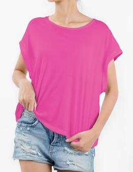 De vrouw die roze t-shirt draagt en scheurt jeans op wit kort