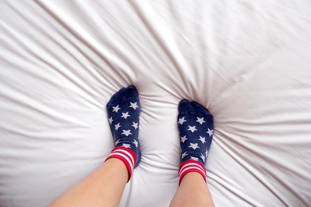 De vrouw die sokken draagt bevindt zich op bed.
