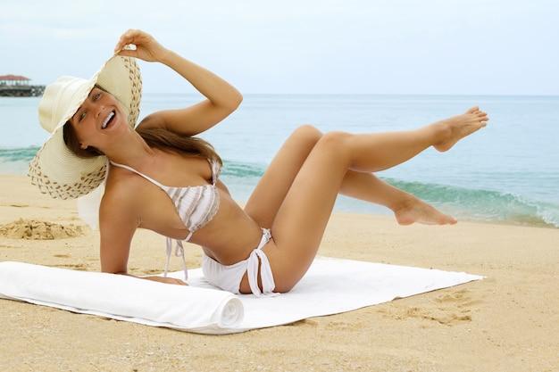 De vrouw die strandhoed draagt zit naast een overzees
