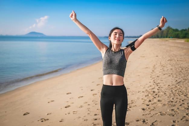 De vrouw die van azië in sportwaren voor het uitoefenen genieten en op het strand lopen.