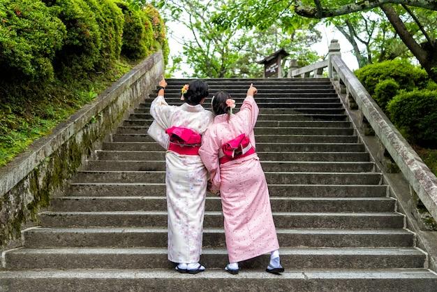 De vrouw die van azië japanse kimono draagt bij tuin.