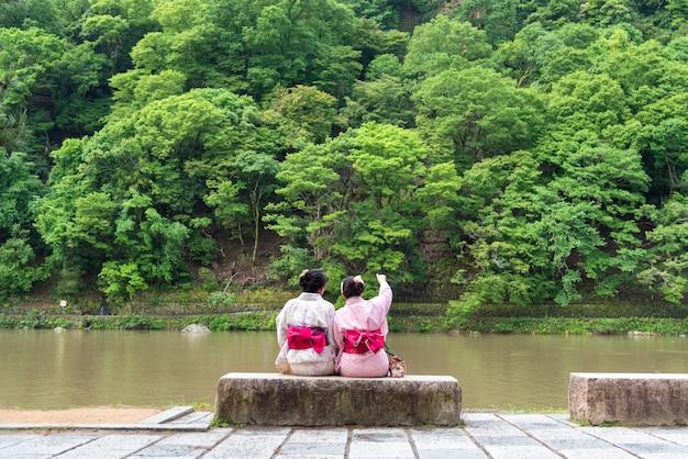 De vrouw die van azië japanse kimono naast een rivier draagt.